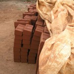 Mud bricks drying under a tarpaulin